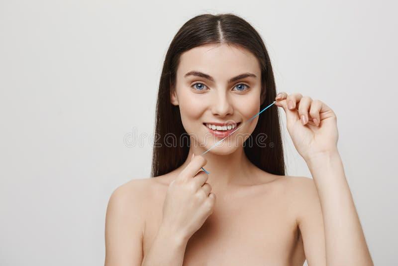 Ta omsorg av det perfekta leendet Studion sköt av den härliga kvinnan som får behandling för tänder med tandtråd som ler royaltyfria foton