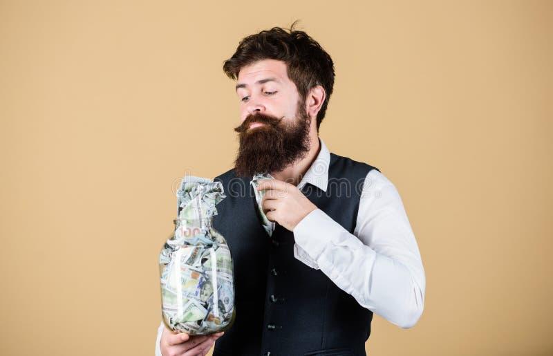 Ta pengar för att göra affär Affärsman som tar pengar ut ur exponeringsglaskruset Skäggig man som sätter investera pengar in arkivfoto