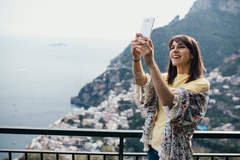 Ta selfie med den främre kameran för smartphone Le seaview för handelsresande för ung kvinna enoying i Positano, Italien Semester royaltyfria foton