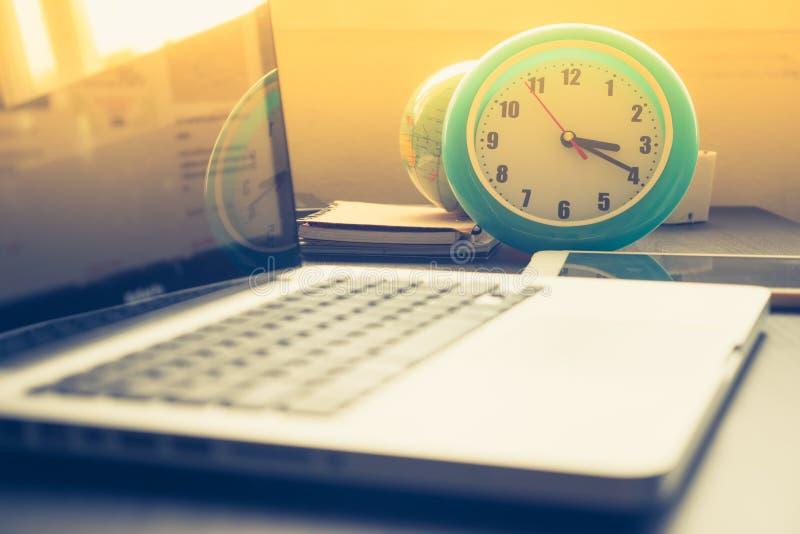 Ta tid på med bärbara datorn på kontorsskrivbordet och solsken i eftermiddag arkivbild