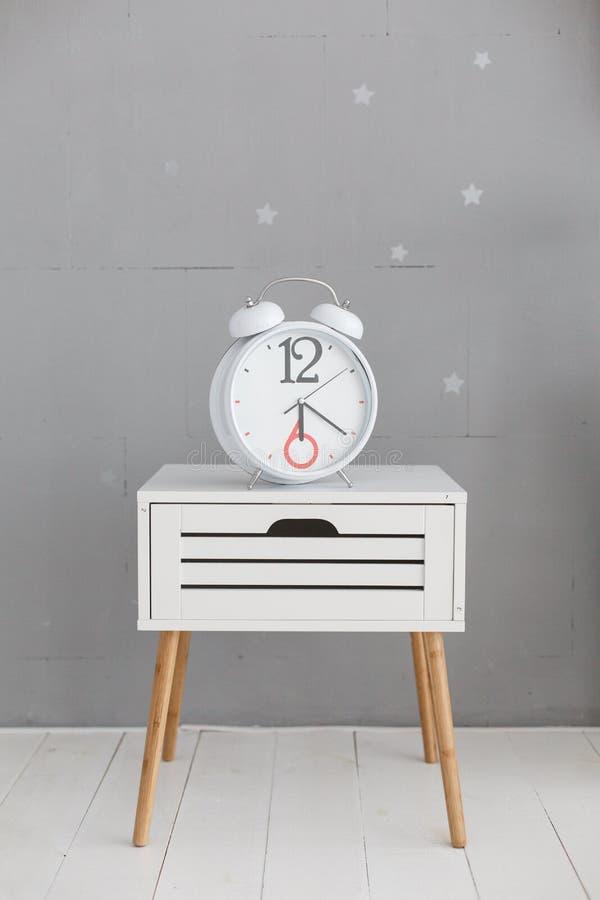 Ta tid på på en near grå vägg för vit nightstand arkivbilder