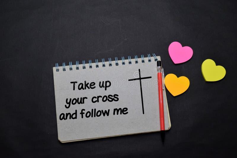 Ta upp ditt korset och följ mig och skriv i en bok på kontoret Begreppet kristen tro royaltyfri foto