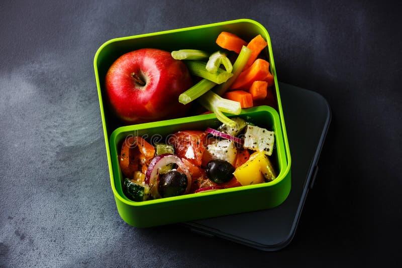 Ta ut mat grekisk sallad och Apple frukt i lunchask arkivfoto