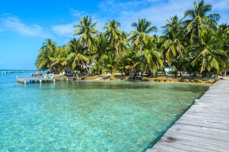 Tabaco Caye - relaj?ndose en el embarcadero de madera en la peque?a isla tropical en la barrera de arrecifes con la playa del par imagenes de archivo