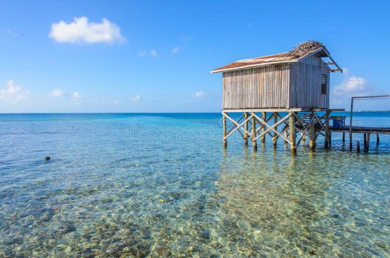 Tabaco Caye - relaj?ndose en la cabina o la casa de planta baja en la peque?a isla tropical en la barrera de arrecifes con la pla foto de archivo libre de regalías
