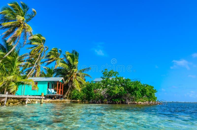 Tabaco Caye - relaj?ndose en la cabina o la casa de planta baja en la peque?a isla tropical en la barrera de arrecifes con la pla imágenes de archivo libres de regalías
