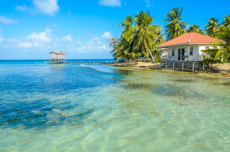 Tabaco Caye - relaj?ndose en la cabina o la casa de planta baja en la peque?a isla tropical en la barrera de arrecifes con la pla fotos de archivo