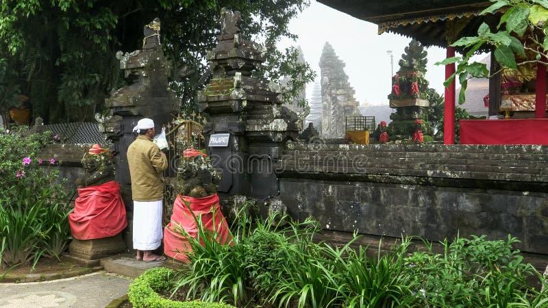 TABANAN, INDONÉSIA JUNHO, 16 2017: tiro largo de um devoto no templo bratan do danu do ulun em bali fotos de stock royalty free