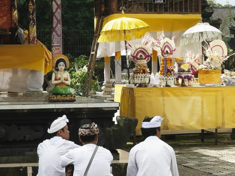 TABANAN, INDONESIË 16 JUNI, 2017: drie liefhebbers zitten en aanbidden bij de bratan tempel van ulundanu, Bali stock afbeelding