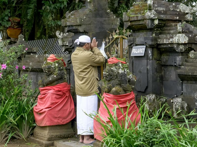 TABANAN INDONESIEN JUNI, 16 2017: nära upp av en hinduisk man som tillber på den bratan ulundanuen, bali royaltyfri bild