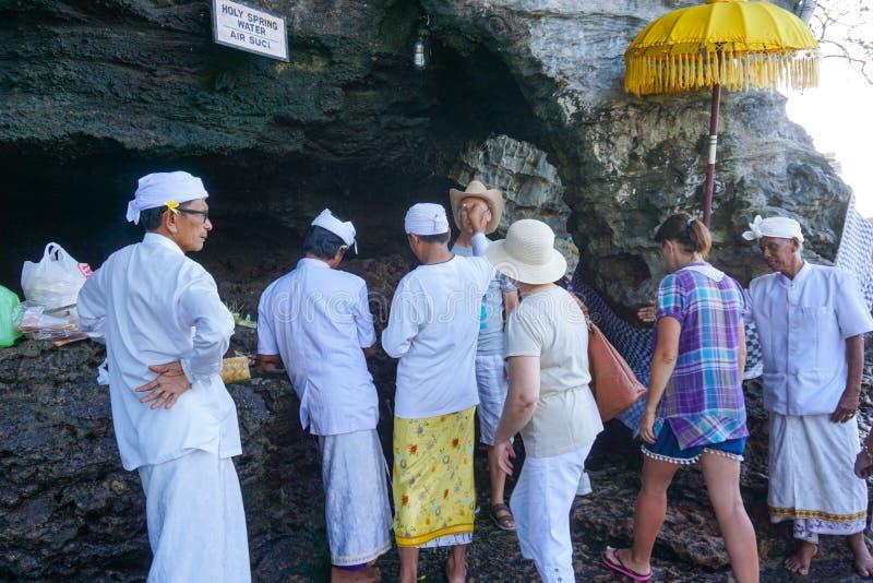 Tabanan Pura Tanah Lot Hindoese tempel die op een eilandje wordt voortgebouwd Een toerist wordt gezegend door een Hindoese priest royalty-vrije stock afbeelding
