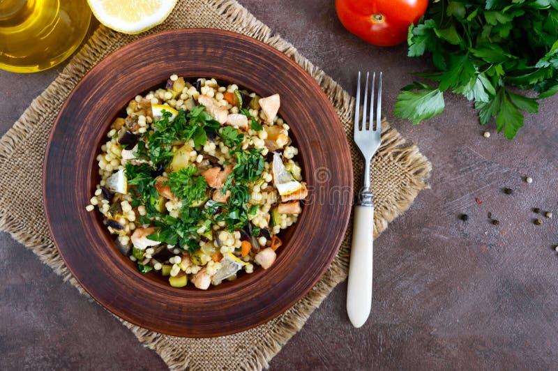 Tabbouleh - hete salade van kouskous, vlees, gebraden groenten en peterselie in een kleikom stock afbeeldingen