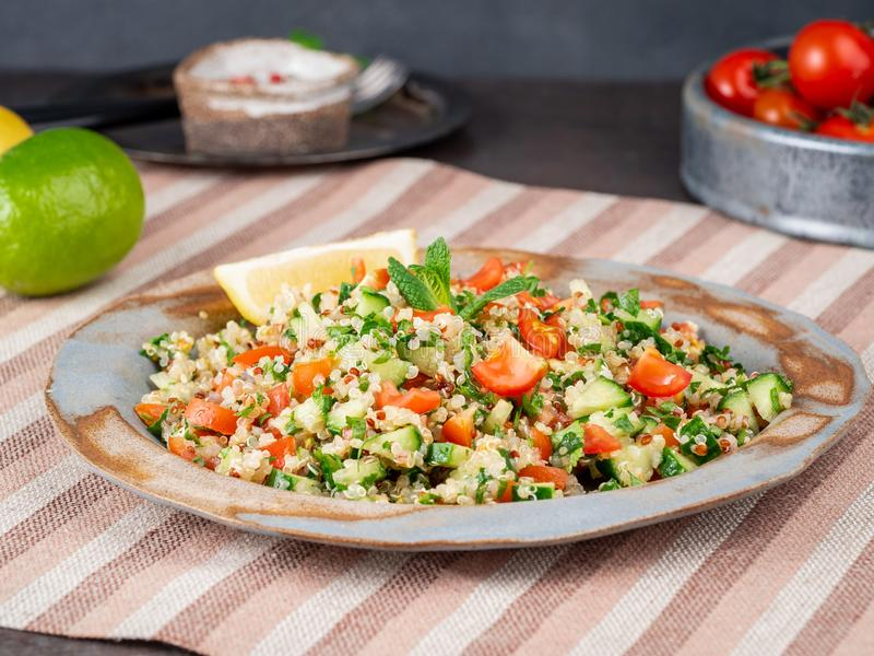 Tabbouleh salad with quinoa. Eastern food with vegetables mix, vegan diet. Side view, linen napkin, old plate royalty free stock photography