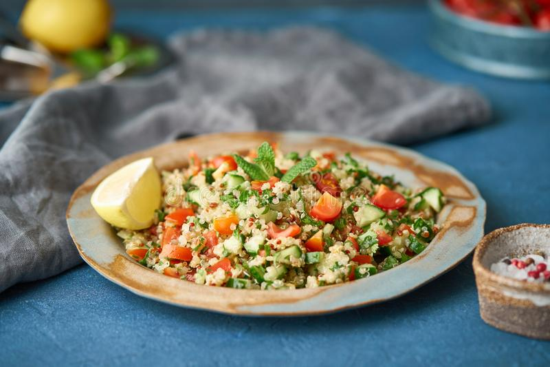 Tabbouleh salad with quinoa. Eastern food with vegetables mix, vegan diet. Side view, old plate royalty free stock image
