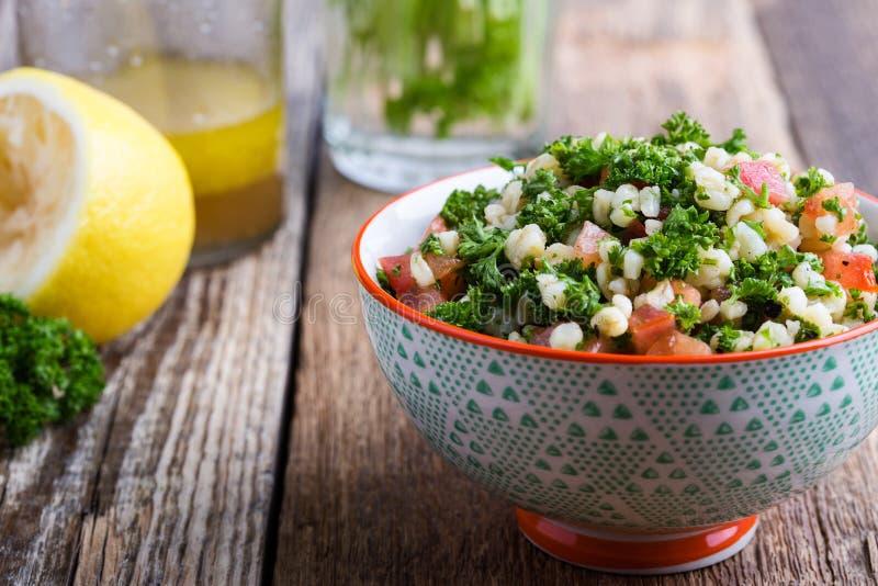 Tabboulehsalade met bulgur, verse peterselie, tomaten en slasaus stock afbeeldingen