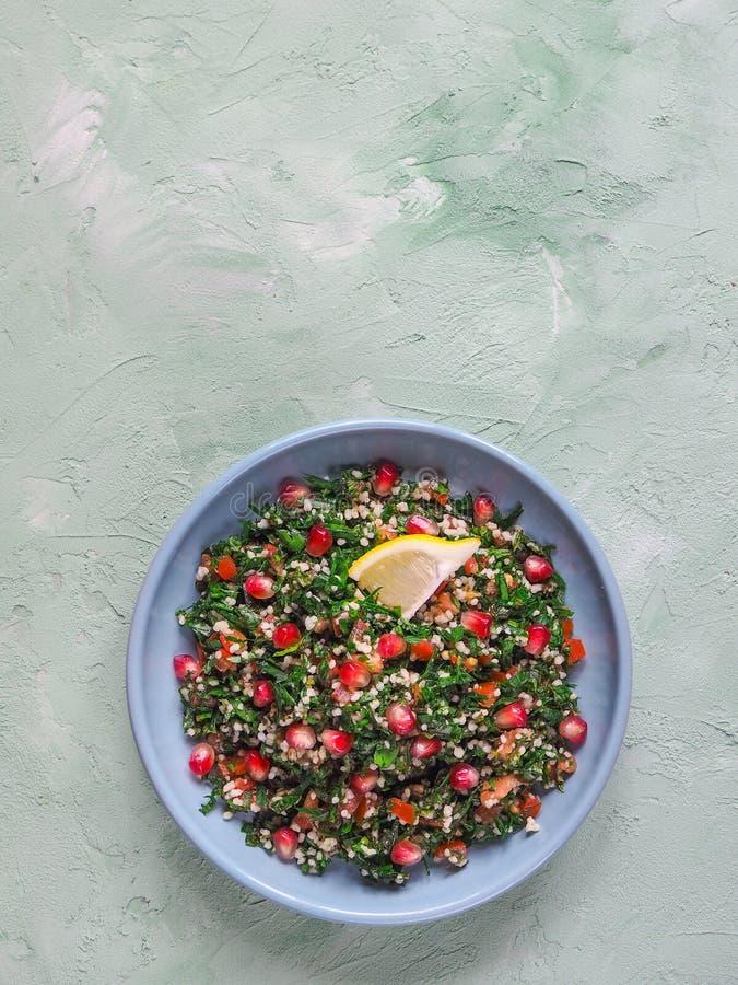 Tabboulehsalade met kouskous in een kom op groene concrete lijst stock foto