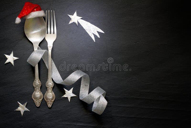 A tabela abstrata do Natal com cutelaria de prata e protagoniza na noite no fundo preto de mármore foto de stock