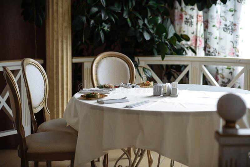 Tabela ajustada para um partido nupcial, uma toalha de mesa branca e um branco com cadeiras do ouro imagem de stock