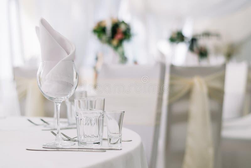 A tabela ajustou-se para um partido ou um copo de água do evento na toalha de mesa branca Fundo macio branco com tabelas e flores imagens de stock royalty free