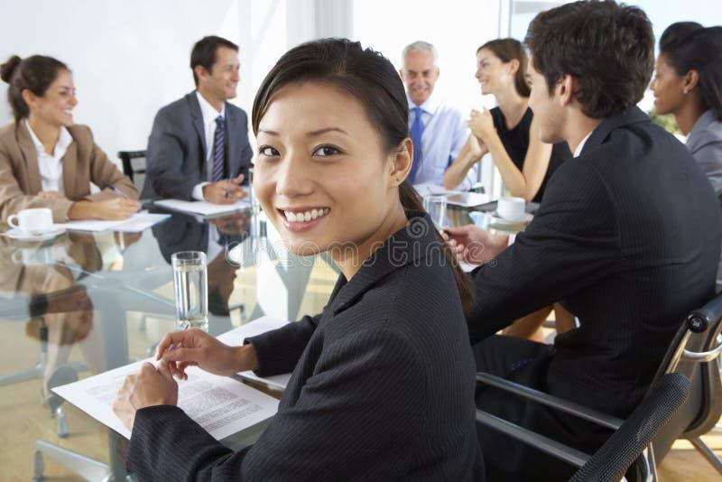Tabela asiática de Sitting Around Boardroom da mulher de negócios com colegas foto de stock