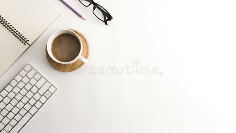 Tabela branca da mesa de escritório com caderno, o computador, fontes e o copo de café vazios foto de stock royalty free