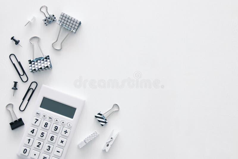 Tabela branca da mesa de escritório com calculadora e outros materiais de escritório Vista superior fotos de stock
