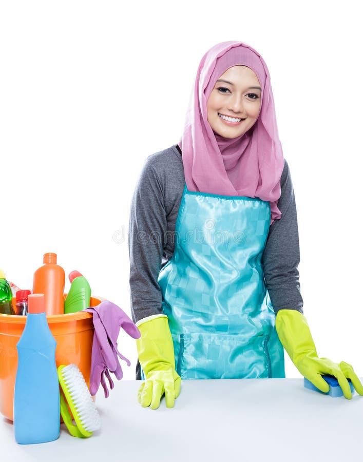 Tabela branca de limpeza vestindo do hijab da jovem mulher usando a esponja imagens de stock royalty free