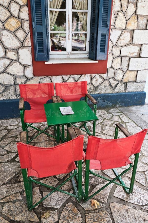 Tabela brilhante do café e cadeiras vermelhas e verdes, Grécia imagem de stock royalty free