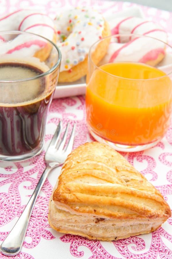 Tabela com anéis de espuma e café da manhã do bolo frito fotografia de stock