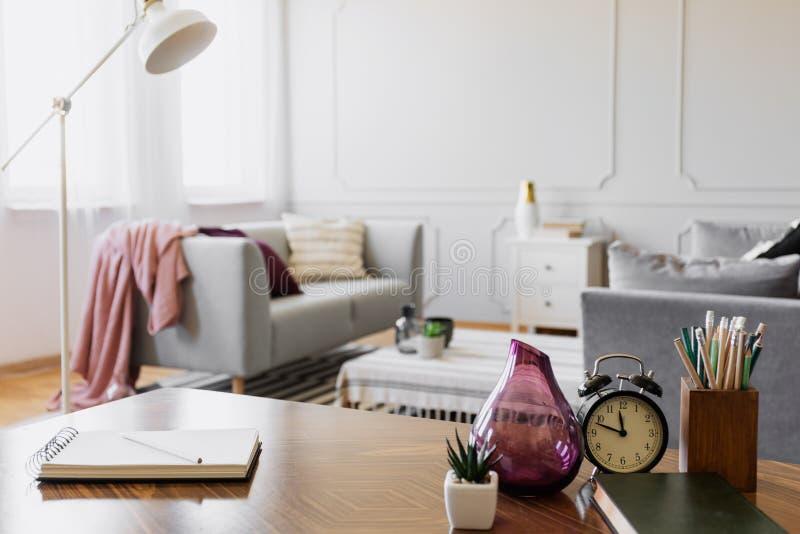 Tabela com caderno, a planta pequena no potenciômetro, o vaso de vidro, o pulso de disparo e os lápis no copo, foto real com espa fotografia de stock