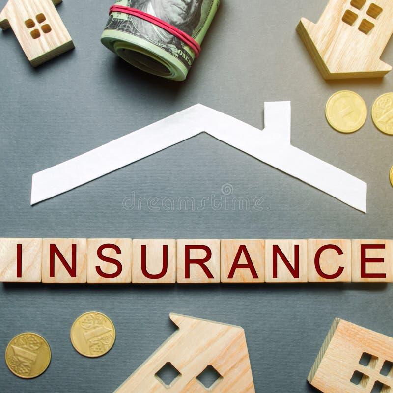 Tabela com casas de madeira, calculadora, moedas, lupa com o seguro da palavra em blocos de madeira O conceito da propriedade imagem de stock