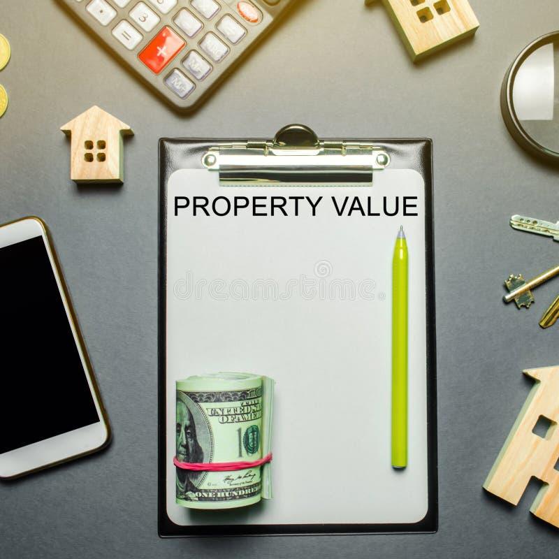 Tabela com casas de madeira, calculadora, moedas, lupa com o valor da propriedade da palavra O contrato para a avalia??o de bens  imagem de stock royalty free