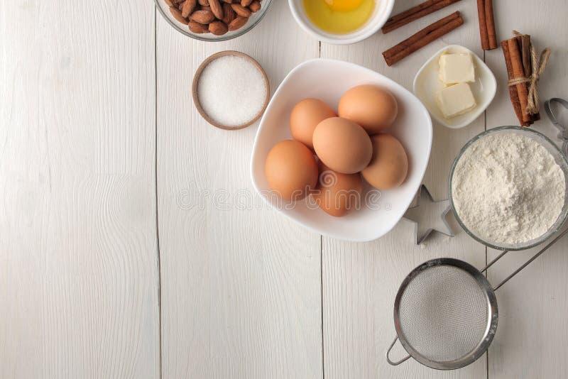 Tabela com ingredientes do cozimento Ferramentas do padeiro para bolinhos manteiga, ovos, açúcar, leite, canela, amêndoas em um f fotografia de stock