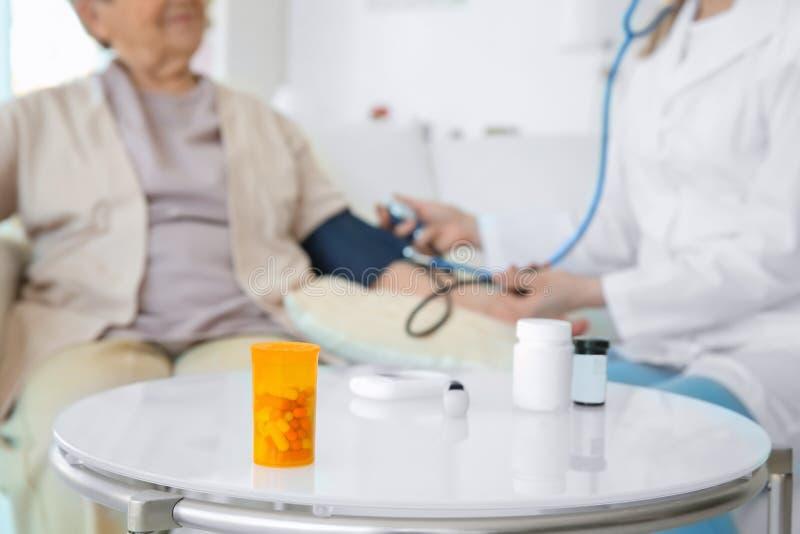 Tabela com medicinas e mulher idosa borrada com enfermeira imagem de stock