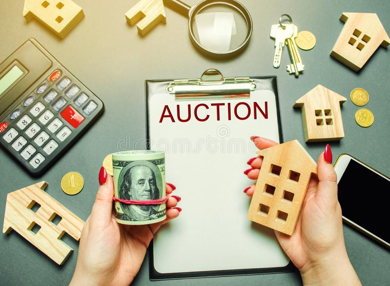 Tabela com o leilão da palavra O leiloeiro das mulheres está guardando o dinheiro nas mãos dos dólares e de uma casa de madeira C fotografia de stock