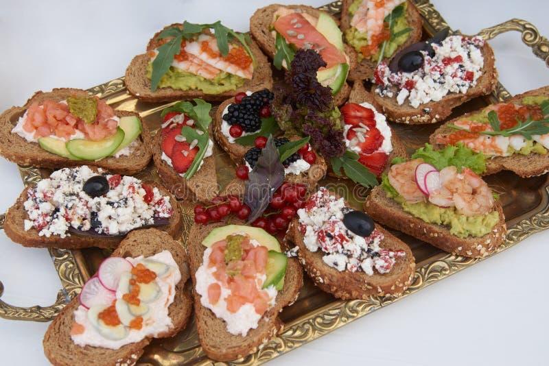 Tabela com os sanduíches frescos dos petiscos, close-up do serviço da restauração do alimento imagem de stock royalty free