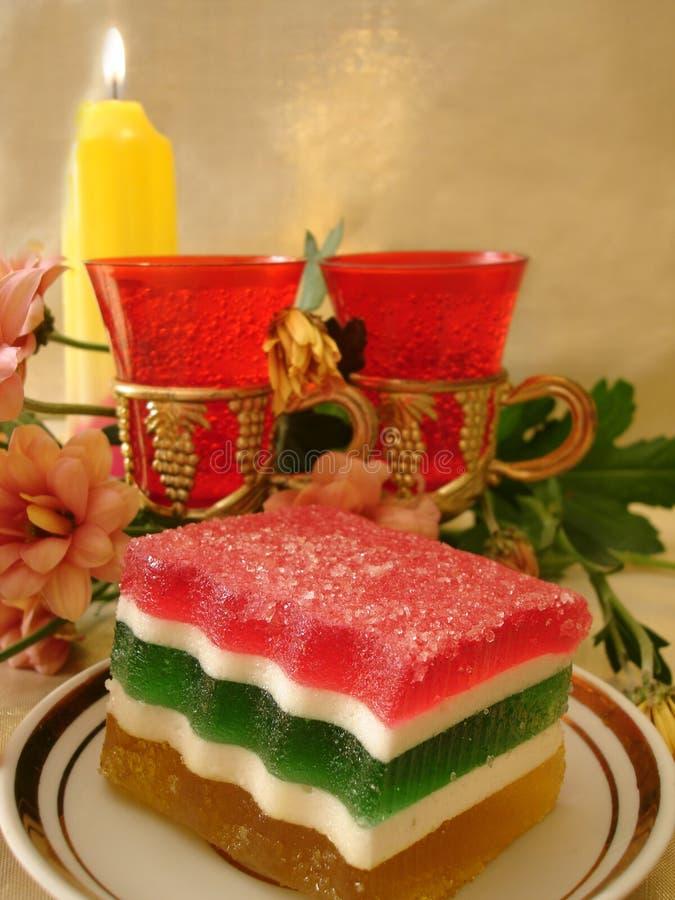 Tabela comemorativo (bolo da geléia da cor na placa, dois vidros vermelhos, f fotos de stock