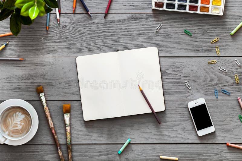 A tabela criativa da arte com o lápis vazio do caderno pinta fontes para esboços do trabalho fotos de stock