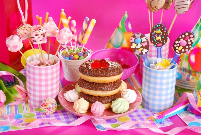 Tabela da festa de anos com flores e doces para crianças fotografia de stock