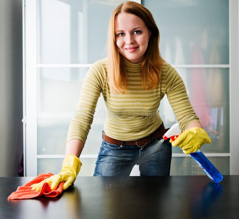 Tabela da limpeza da menina com polimento da mobília em casa foto de stock