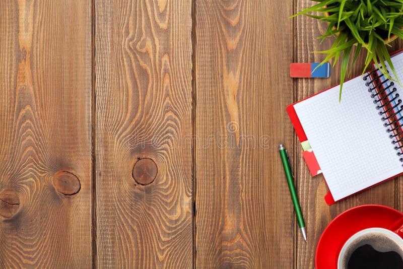 Tabela da mesa de escritório com fontes, copo de café e flor imagem de stock