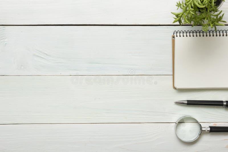 Tabela da mesa de escritório com fontes Vista superior Copie o espaço para o texto Bloco de notas, pena, lupa, flor fotos de stock royalty free