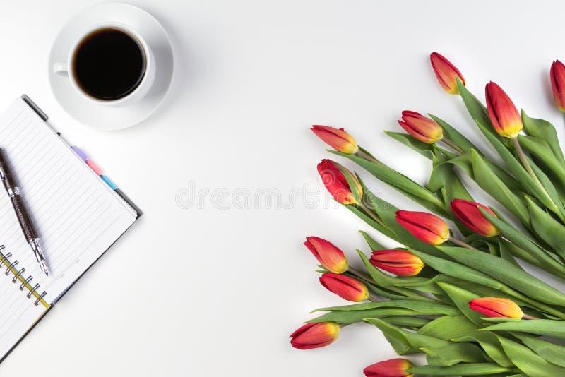 Tabela da mesa de escritório com o caderno de papel aberto, a pena, o copo de café e grupo fresco bonito de tulipas das flores foto de stock royalty free