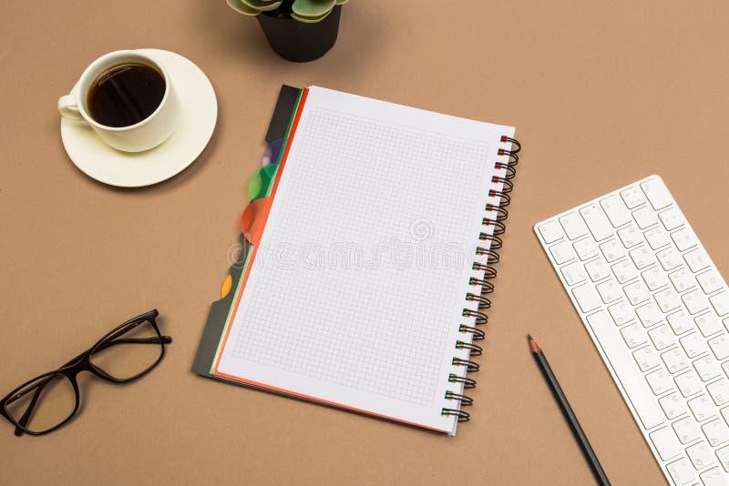 Tabela da mesa de escrit?rio com o caf? e os vidros do teclado do caderno trocistas acima do molde Vista superior foto de stock royalty free