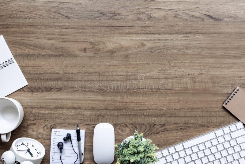 Tabela da mesa de escritório com o copo do teclado, das fontes, da flor e de café imagem de stock royalty free