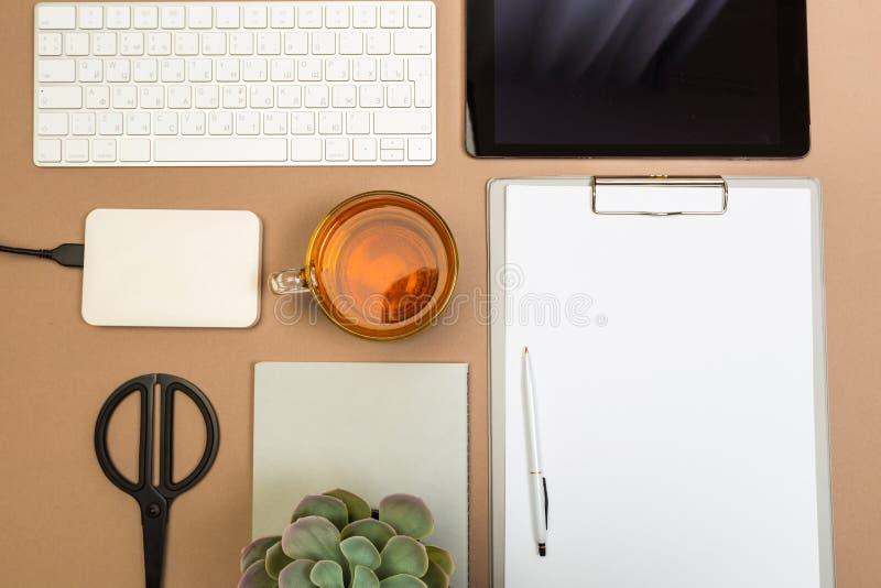 Tabela da mesa de escritório com o disco e as tesouras do copo de chá do caderno do teclado da prancheta da tabuleta Zombaria aci imagens de stock royalty free