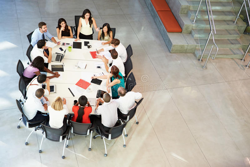 Tabela da sala de reuniões de Addressing Meeting Around da mulher de negócios fotografia de stock