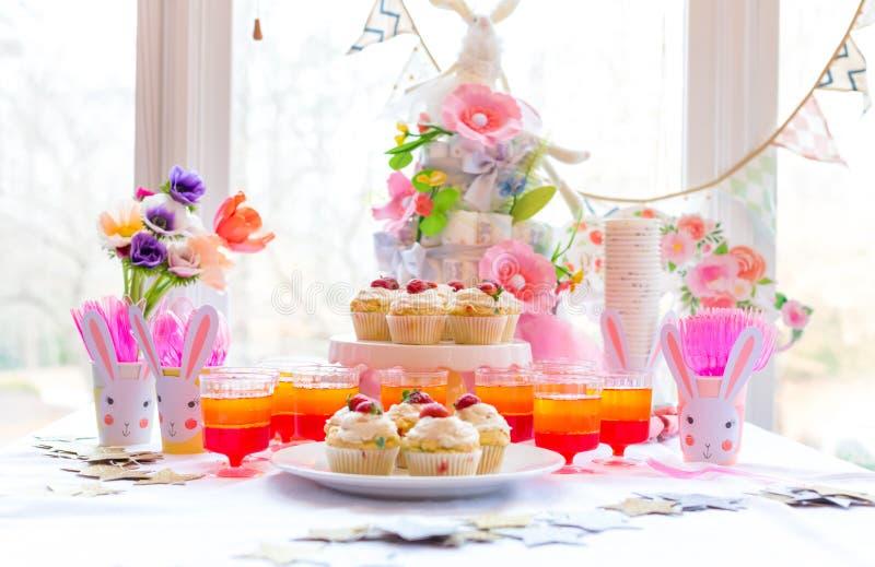 Tabela da sobremesa com queques e flores fotos de stock royalty free