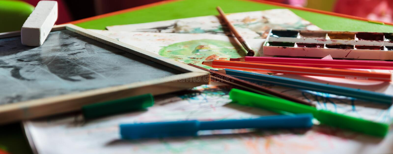 A tabela das crianças com pinturas, Livro Branco e giz para tirar fotos de stock