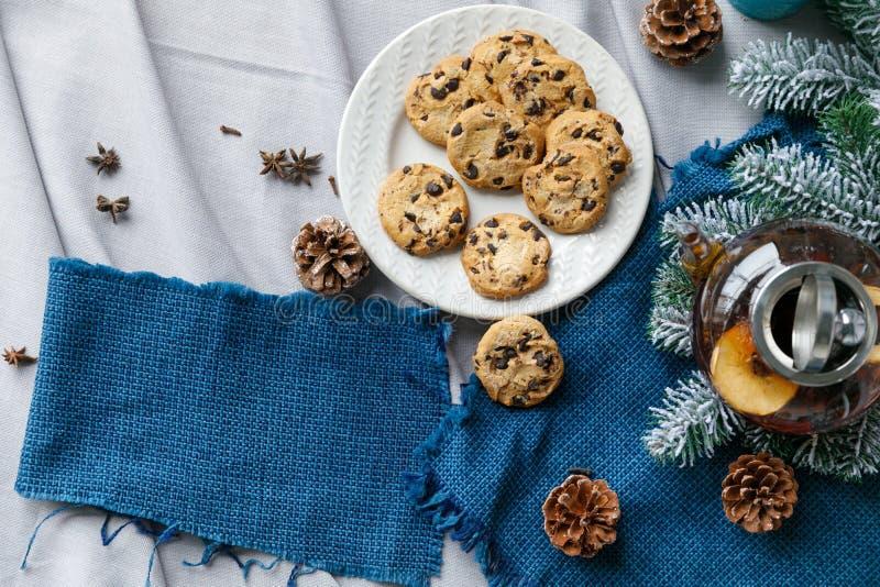 A tabela de ano novo com ramos e decorações do abeto em um fundo de madeira Chá com cookies, pão-de-espécie do Natal fotografia de stock royalty free